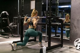 Smith machine lunges done by a girl at the gym